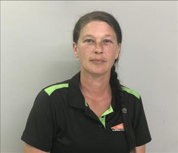 Headshot of half-smiling woman wearing a SERVPRO uniform in front of a gray background