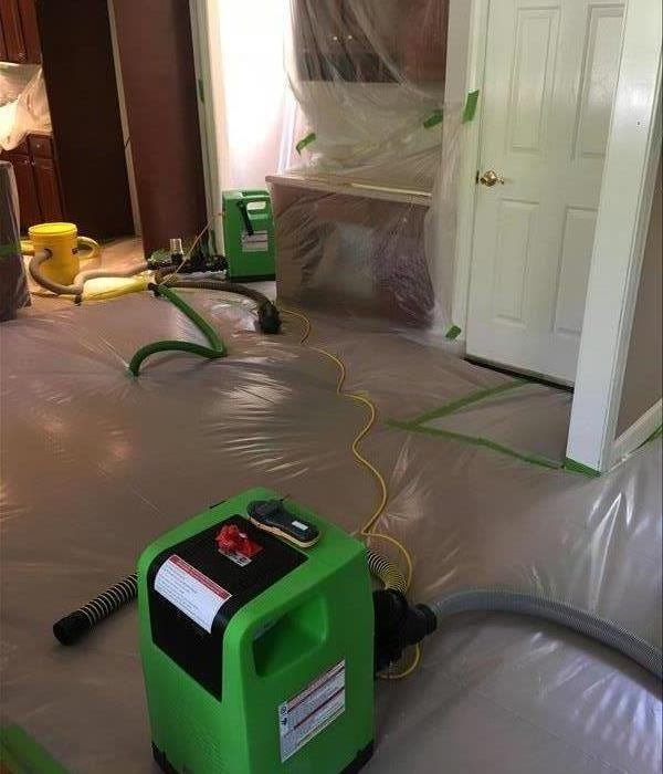 Plastic and dehumidifiers covering hardwood floors in a home