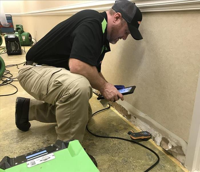 SERVPRO employee places a moisture meter against a  wall