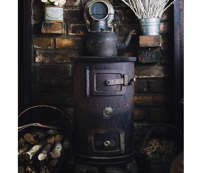 Antique furnace beside wood pile and in front of brick wall