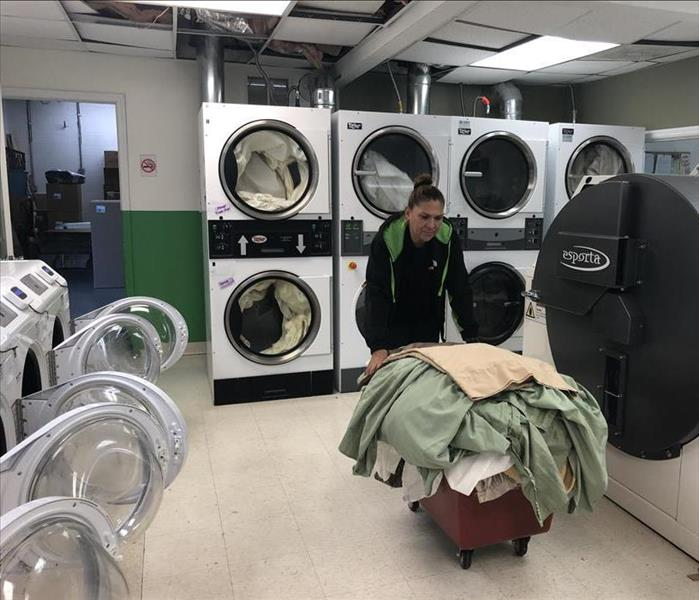 SERVPRO employee pushing a cart of clothes in a textile cleaning facility