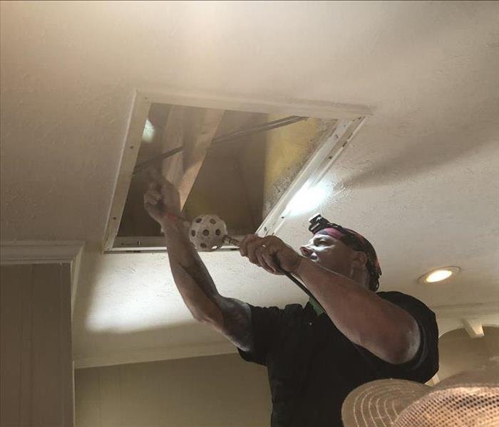 SERVPRO Technician Blowing Debris Out of an Air Vent